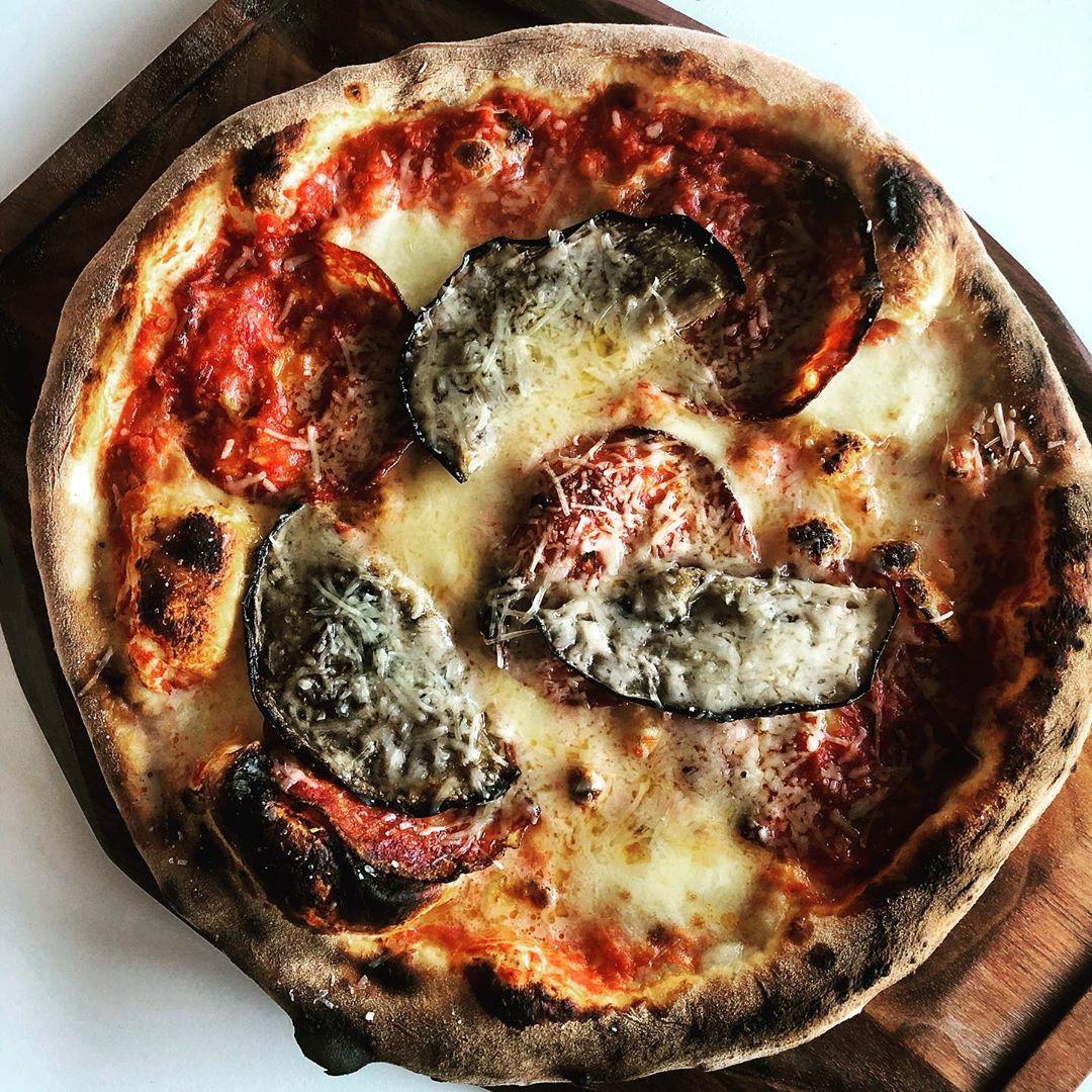 Pizza med stærk salami, aubergine og parmesan